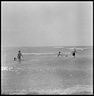 Women in waist-deep water wade against the waves circa 1950