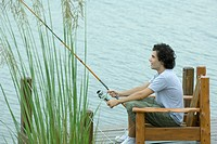 Young man fishing on dock