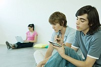 Teenage friends sitting on floor, one writing in notebook (thumbnail)