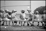 Young boys sit on bench during a little league baseball game