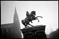 Silhouetted view of European equestrian sculpture in city plaza