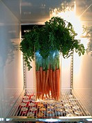 Glass vase filled with carrots sits in refrigerator