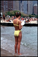 Woman in yellow bikini reads book with feet in water