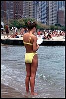 Woman in yellow bikini reads book with feet in water