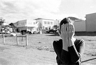 Woman standing outdoors covering face with hands