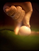 Tight angle of gloved hand removing golf ball from cup