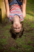 Young girl hanging from monkey bars