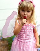 Young girl dressed as fairy princess, sucking lollipop