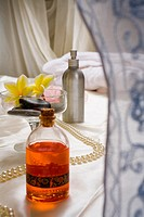 Spa elements, Bottle of pink bath gel, flowers and stones in glass, string of pearls