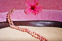 Spa elements, string of small pink shells layed over a bowl filled with sand and a pink towel with a pink hibiscus