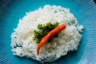 Close-up of a red chili and green garnish on a bed of steamed white rice