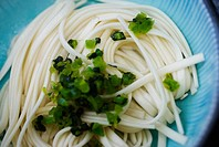 Close-up of chopped green asian vegetable on a bed of Japanese soba noodles