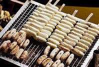 Thailand, Bangkok, unusual delicacies found at street vendor food stalls, closeup of bananas cooking on the grill