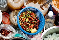 Thailand, Bangkok, Close-up of a bowl of chili peppers among other sauces and ingrediants at a street food stall