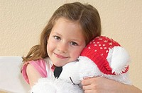 headshot of little girl holding cuddly toy in shape of polar bear