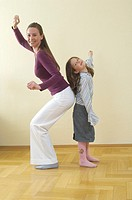 full body portrait of mother and young daughter standing back to back having fun