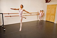 Hispanic/black girl wearing pink leotard practices the First Arabesque position in ballet class.