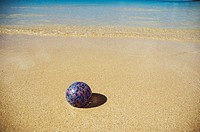 Art glass float on sandy beach with calm ocean