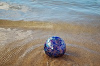 Art glass float in shallow ocean water sandy beach