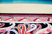 Detail of ornate design on beach towel on beach, ocean background (thumbnail)