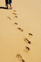 Footprints in sand with legs wearing jeans and feet at top of picture (thumbnail)