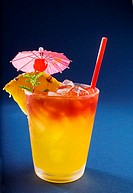 A tropical drink garnished with fruit and flowers