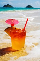 A mai tai garnished with pinapple and a cherry, sitting in shallow water on the beach