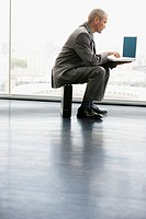 Businessman Sitting on a Briefcase Using a Laptop