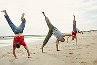 Young Friends Performing Somersaults on Beach