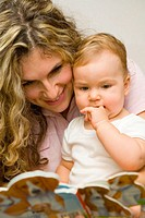 Blonde young mother with her baby girl looking at picture book