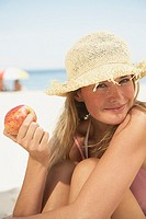 Young woman in sun hat with apple
