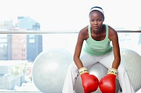 Woman sitting on fitness ball wearing boxing gloves