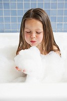 Girl playing in bubble bath