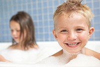 Boy taking a bubble bath, sister in background