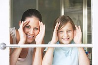 Mother and daughter looking out glass door