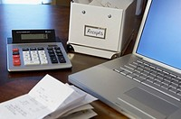 Receipts with calculator and laptop computer