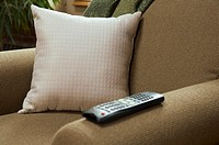 Pillow and remote control on arm chair