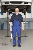 Friendly mechanic standing in front of hoisted car