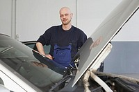 Mechanic standing behind car with hood raised