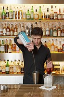 Bartender pouring drinks behind bar