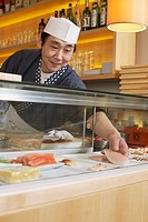 Sushi chef reaches for piece of seafood