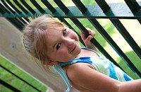 Portrait of a young girl standing next to a metal gate, smiling