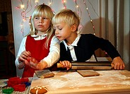 A boy and a girl roll out the paste  They bake ginger biscuits for Christmas