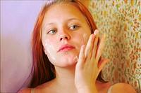 Girl adding moisturizing lotion