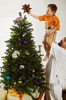 Mature man lifting his son to decorate a Christmas tree