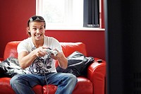 Man sitting on the couch playing video game console (thumbnail)