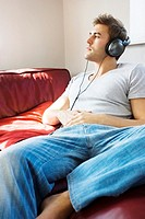 Man lying on the bed listening to music on the headphones
