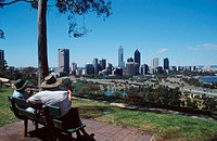 Couple, sitting, on, bench, at, Victoria, park, with, view, on, the, skyline, of, Perth, Western, Australia, Paar, sitzt, auf, einer, Bank, im, Victor...