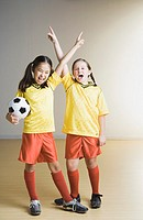 Two girls cheering in soccer outfits