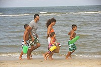 Hispanic family running on beach